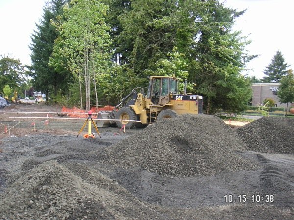 Placing base rock in the parking lot area north of Hickory Street